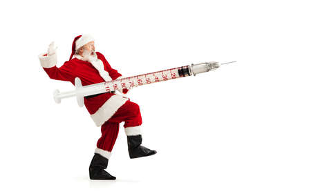 Santa Claus holding huge vaccine against COVID like Christmas gift isolated on white background. Male model in traditional costume. New Year, holidays, winter, epidemic, pandemic concept. Copyspace.