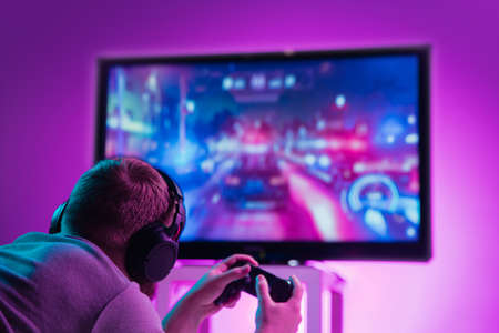 Back view shot of professional gamer playing online video game on his gameset. Room lit in neon light and retro style. Using headphones to talk with the team. Entertainment, fun concept.