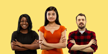 Group portrait of emotional people on yellow studio background. Flyer, collage made of 3 models. Concept of human emotions, facial expression, sales, ad. Successful hands crossing, confident.