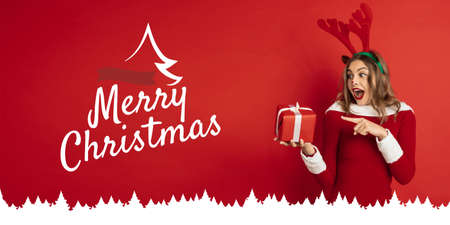 Greeting flyer for ad. Concept of Christmas, 2021 New Years, winter mood, holidays. Copyspace, postcard. Beautiful caucasian woman like Santas Rudolph the Red-Nosed Reindeer pointing on gift. Stock Photo