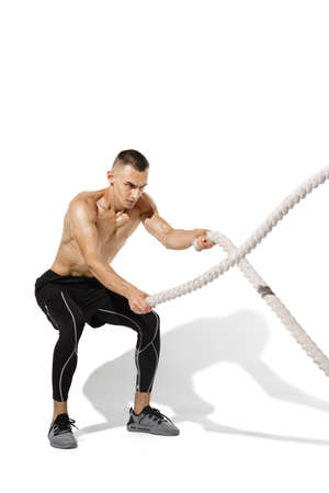 Ropes. Stylish young male athlete practicing on white studio background, portrait with shadows. Sportive fit model in works out in motion and action. Body building, healthy lifestyle, style concept. Stock fotó