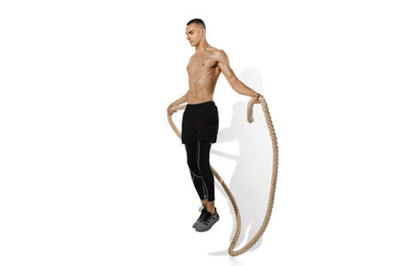 Jumping with rope. Stylish young male athlete practicing on white studio background, portrait with shadows. Sportive fit model in motion and action. Body building, healthy lifestyle, style concept. Stock fotó