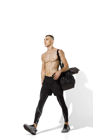 Before workout. Stylish young male athlete on white studio background, portrait with shadows. Sportive fit model in motion and action. Body building, healthy lifestyle, style concept.