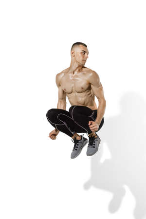 Jumping high. Stylish young male athlete practicing on white studio background with shadows. Sportive fit model in works out in motion and action. Body building, healthy lifestyle, style concept. Stock fotó