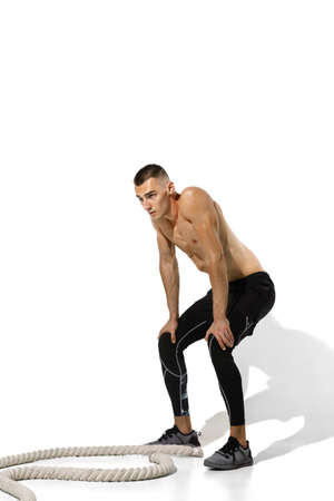Resting, confident. Stylish young male athlete on white studio background, portrait with shadows. Sportive fit model in motion and action. Body building, healthy lifestyle, style concept. Stock fotó
