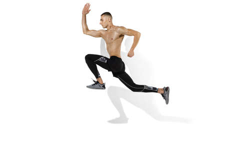 Running, jumping high. Stylish young male athlete on white studio background, portrait with shadows. Sportive fit model in motion and action. Body building, healthy lifestyle, style concept.