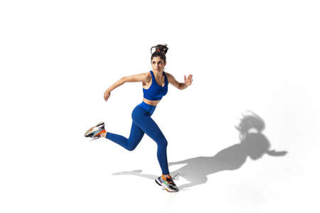 Movement. Beautiful young female athlete practicing on white studio background, portrait with shadows. Sportive fit model in motion and action. Body building, healthy lifestyle, style concept. Banco de Imagens