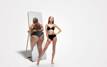 Young fit, slim woman looking at fat girl in mirrors reflection on white background. Thinking shes not enough sportive. Concept of healthy lifestyle, fitness, sport, nutrition and body positive.