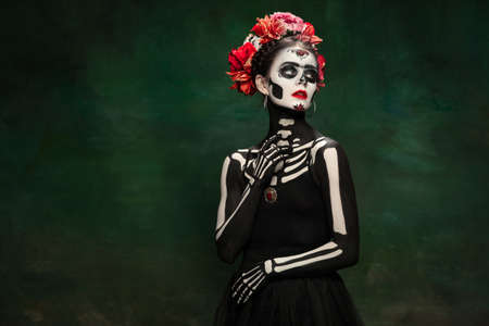 Scary. Young girl like Santa Muerte Saint death or Sugar skull with bright make-up. Portrait isolated on dark green studio background with copyspace. Celebrating Halloween or Day of the dead. Stock fotó