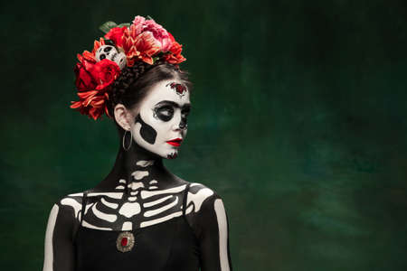 Passioned. Young girl like Santa Muerte Saint death or Sugar skull with bright make-up. Portrait isolated on dark green studio background with copyspace. Celebrating Halloween or Day of the dead.