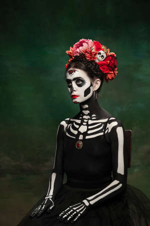 Bright. Young girl like Santa Muerte Saint death or Sugar skull with bright make-up. Portrait isolated on dark green studio background with copyspace. Celebrating Halloween or Day of the dead.