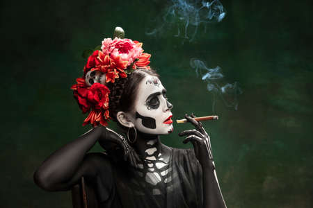 Smoke. Young girl like Santa Muerte Saint death or Sugar skull with bright make-up. Portrait isolated on dark green studio background with copyspace. Celebrating Halloween or Day of the dead. Stock fotó