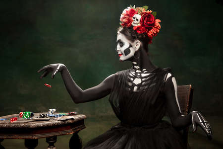 Casino. Young girl like Santa Muerte Saint death or Sugar skull with bright make-up. Portrait isolated on dark green studio background with copyspace. Celebrating Halloween or Day of the dead.