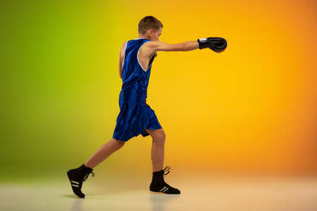 Stronger. Teenage professional boxer training in action, motion isolated on gradient background in neon light. Kicking, boxing. Concept of sport, movement, energy and dynamic, healthy lifestyle.