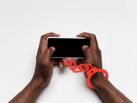 Hand using phone, device on top view. Addicted man, wired with chain to social media or games playing. Copyspace for ad on screen. Technologies, modern, marketing, online. White color on background.