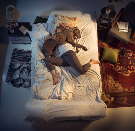 Portrait of a woman, female breeder sleeping in the bed with her dog at home. Top view. Dressed housekeeper sleeping after tiring work day. Holding his pet close to. Job, work, pets love concept.