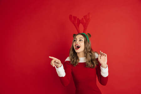 Pointing. Greetingcard. Concept of Christmas, 2021 New Years, winter mood, holidays. Copyspace for ad, postcard. Beautiful caucasian woman with long hair like Santas Reindeer catching giftbox. Stock Photo