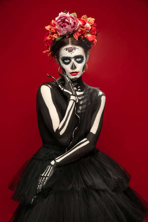 Scary. Young girl like Santa Muerte Saint death or Sugar skull with bright make-up. Portrait isolated on red studio background with copyspace. Celebrating Halloween or Day of the dead.