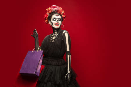 Shopping. Young girl like Santa Muerte Saint death or Sugar skull with bright make-up. Portrait isolated on red studio background with copyspace. Celebrating Halloween or Day of the dead. Black friday.