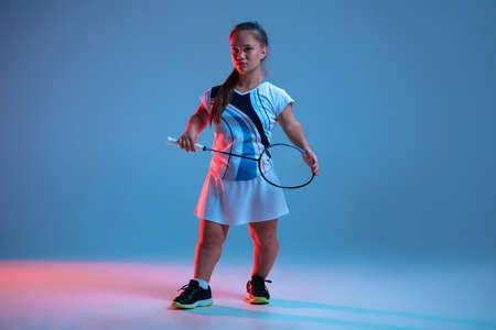 Leader. Beautiful dwarf woman practicing in badminton isolated on blue background in neon light. Lifestyle of inclusive people, diversity and equility. Sport, activity and movement. Copyspace for ad.