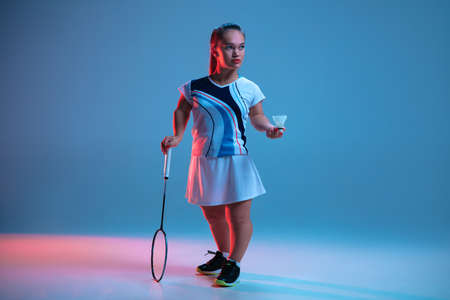 Leader. Beautiful dwarf woman practicing in badminton isolated on blue background in neon light. Lifestyle of inclusive people, diversity and equility. Sport, activity and movement. Copyspace for ad. Stock Photo