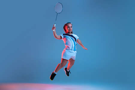 Action. Beautiful dwarf woman practicing in badminton isolated on blue background in neon light. Lifestyle of inclusive people, diversity and equility. Sport, activity and movement. Copyspace for ad. Stock Photo