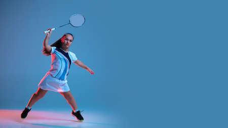 Motion. Beautiful dwarf woman practicing in badminton isolated on blue background in neon light. Lifestyle of inclusive people, diversity and equility. Sport, activity and movement. Copyspace, flyer Stock Photo