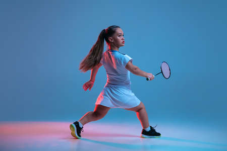 Motion. Beautiful dwarf woman practicing in badminton isolated on blue background in neon light. Lifestyle of inclusive people, diversity and equility. Sport, activity and movement. Copyspace for ad.