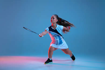 Motion. Beautiful dwarf woman practicing in badminton isolated on blue background in neon light. Lifestyle of inclusive people, diversity and equility. Sport, activity and movement. Copyspace for ad. Stock Photo