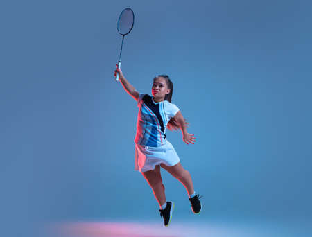 Winner. Beautiful dwarf woman practicing in badminton isolated on blue background in neon light. Lifestyle of inclusive people, diversity and equility. Sport, activity and movement. Copyspace.