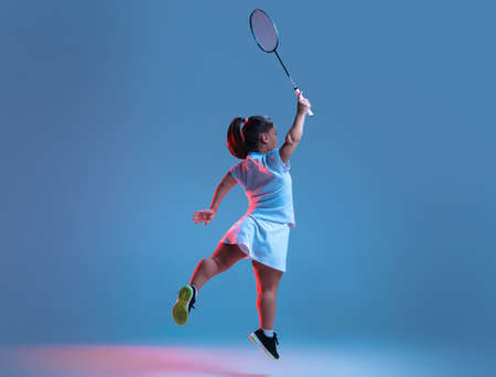 Strong. Beautiful dwarf woman practicing in badminton isolated on blue background in neon light. Lifestyle of inclusive people, diversity and equility. Sport, activity and movement. Copyspace. Stock Photo