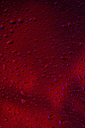 Close up view of cold drops on the glass of beer background. Texture of cooling alcohol drink with macro bubbles on the glass wall. Fizzing or floating up to top of surface. Dark brown colored. Standard-Bild