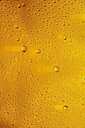 Close up view of cold drops on the glass of beer background. Texture of cooling alcohol drink with macro bubbles on the glass wall. Fizzing or floating up to top of surface. Golden colored.