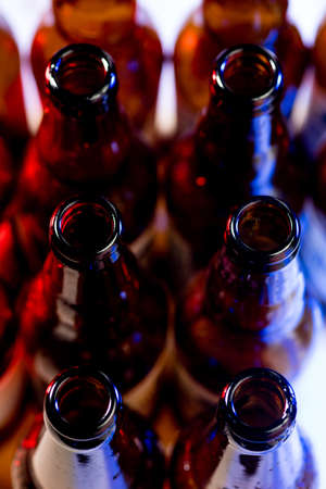 Dark. Neon colored beer bottles, close up isolated on bright studio background. Concept of beer, beverage, entertainment and alcohol. Copyspace for your bar, restaurant, brewery or shop advertising.