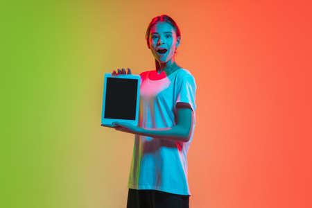 Showing tablets screen. Young caucasian girls portrait on gradient green-orange studio background in neon light. Concept of youth, human emotions, facial expression, sales, ad. Beautiful teen model.