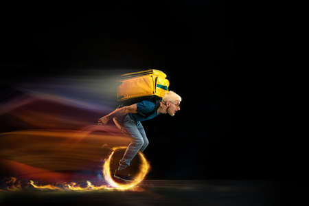 One the go. Fast delivery service - deliveryman on unicycle driving with order in fire on dark background. Copyspace for ad. Super fast shipping of food and goods orders during quarantine.