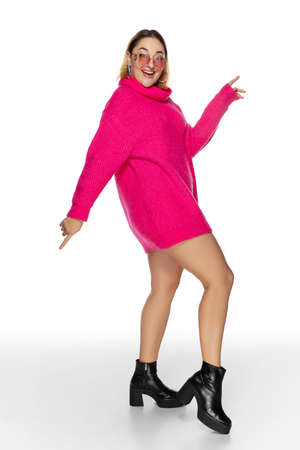 Dance. Beautiful young woman bright pink comfortable sweater, long sleeve isolated on white studio background. Magazine style, fashion, beauty concept. Fashionable posing. Copyspace for ad. Stock Photo