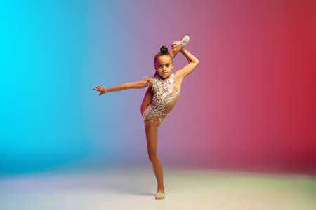 Energy. Little caucasian girl, rhytmic gymnast training, performing isolated on gradient blue-red studio background in neon. Graceful and flexible, strong child. Concept of sport, motion, action. Reklamní fotografie