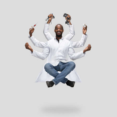 Handsome african doctor, multi-armed man levitating isolated on grey studio background with equipment. Concept of professional occupation, work, job, medicine, healthcare. Multi-task like Shiva.