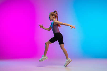 Active. Teenage girl, professional runner, jogger in action, motion isolated on gradient pink-blue background in neon light. Concept of sport, movement, energy and dynamic, healthy lifestyle.