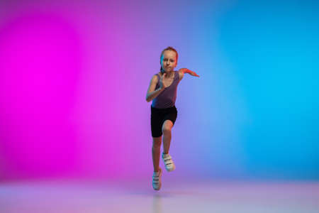 Playful. Teenage girl, professional runner, jogger in action, motion isolated on gradient pink-blue background in neon light. Concept of sport, movement, energy and dynamic, healthy lifestyle.