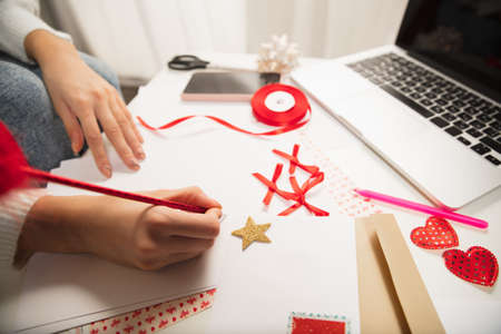 Close up female hands making greeting card for New Year and Christmas 2021 for friends or family, scrap booking, DIY. Writing a letter with best wishes, design her homemade card. Holidays, celebration. 版權商用圖片