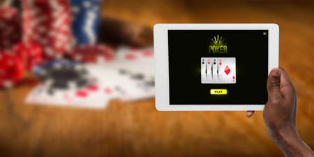Online gambling, casino concept. Hand holding device with lottery, casino cover. Playing dips and cards on table on the background. Poker, bookmaking, gaming, modern technologies, business and finance.