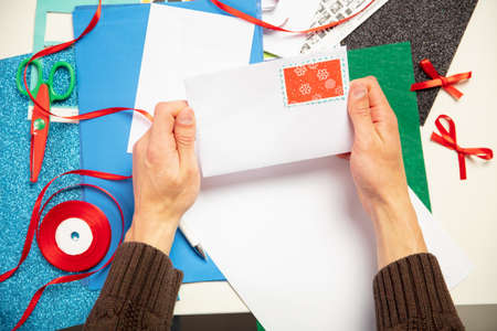 Close up male hands making greeting card for New Year and Christmas 2021 for friends or family, scrap booking, DIY. Writing a letter with best wishes, design his homemade card. Holidays, celebration.