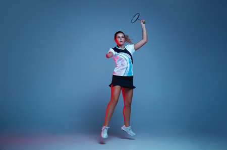 In jump. Beautiful handicap woman practicing in badminton isolated on blue background in neon light. Lifestyle of inclusive people, diversity and equility. Sport, activity and movement. Copyspace.