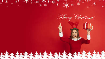 Greeting flyer for ad. Concept of Christmas, 2021 New Years party, winter mood, holidays. Copyspace, postcard. Beautiful caucasian woman in like Santas Deer giving gifts and laughting, pointing