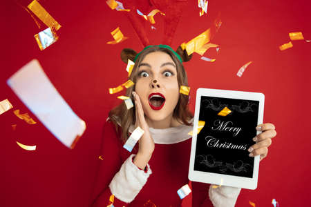 Greeting flyer for ad. Concept of Christmas, 2021 New Years party, winter mood, holidays. Copyspace, postcard. Beautiful caucasian woman in like Santas Deer holding tablet with Merry Chrtistmas screen