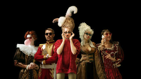 Medieval people as a royalty persons in vintage clothing and modern eyewear using devices on dark background. Concept of comparison of eras, modernity and renaissance, baroque style. Creative collage.