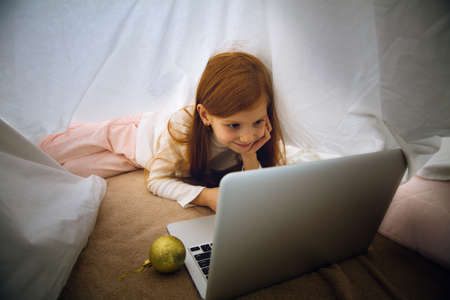 Wishes. Happy caucasian little girl during video call with laptop and home devices, looks dreamful and happy. Talking to Santa before New Years eve, her family, watching cartoons, typing text. Bokeh