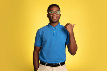 Pointing, showing. Young african-american mans portrait isolated on yellow studio background, facial expression. Beautiful male portrait with copyspace. Concept of human emotions, facial expression.